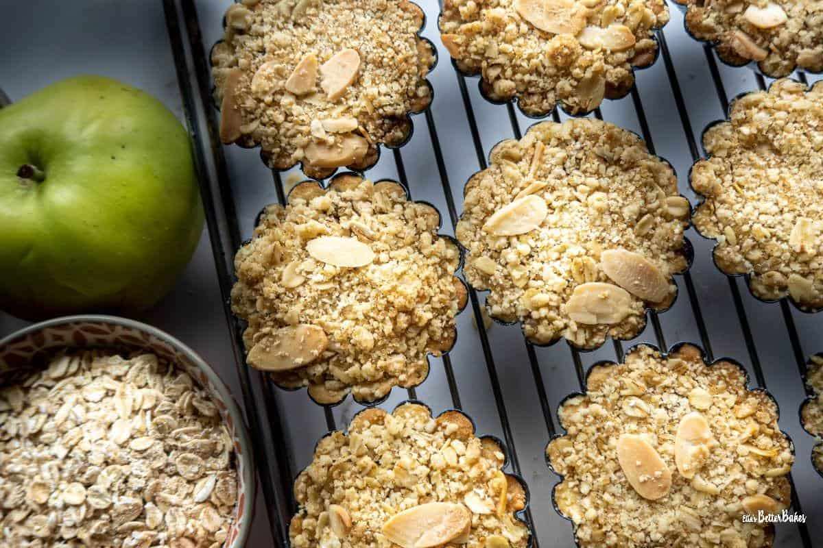 apple crumble tartlets on cooling rack next to ingredient