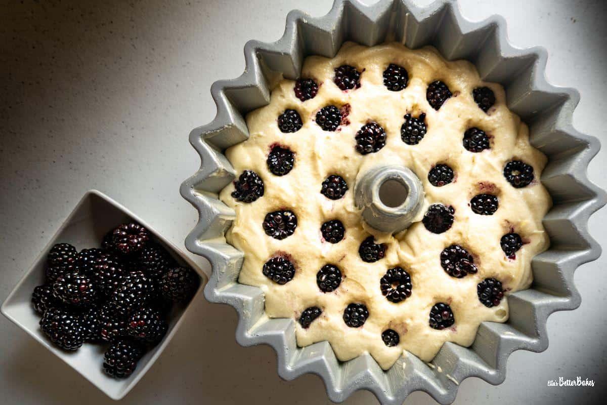 lemon and blackberry cake in tin ready to bake