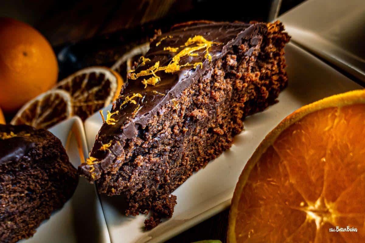 slice of a piece of chocolate orange cake next to an orange